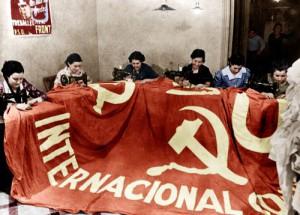 Des membres des Brigades Internationales Communistes (anti-franquistes) realisent un grand drapeau avec la faucille et le marteau pendant la Guerre civile d'Espagne en 1936  ----  Making of a flag for the International Communist Brigade (anti-francoist) during the spanish civil war in 1936 colorized document