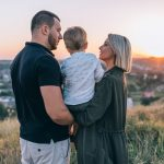 kobieta i mężczyzna trzymają dziecko i spoglądają na zachód słońca